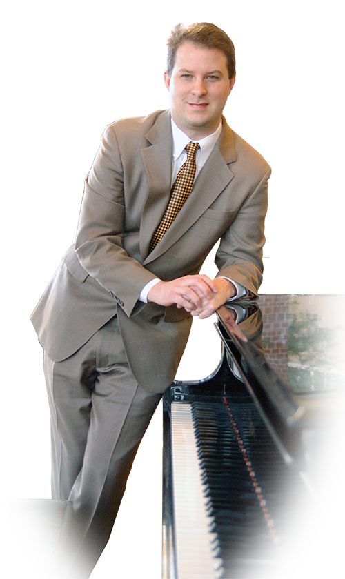 Picture of Michael Gray standing near piano